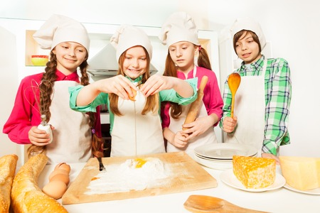 Four young cooks, boy and girls in aprons and cooks hats, learning to prepare bakery dough in the kitchen Stock Photo