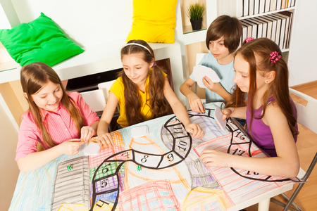 Top view of four kids sitting at the table, playing the tabletop game with cards