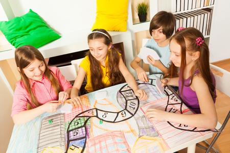 Bovenaanzicht van vier kinderen aan de tafel zitten, spelen de tafelblad met kaarten Stockfoto