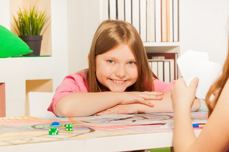 opponent: Happy  ten years old girl, little winner, having rest after playing cards with her opponent Stock Photo