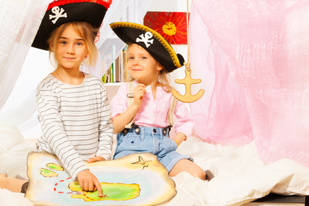 pirata mujer: Dos niñas que llevan los sombreros de tres picos, que juegan los piratas, en busca de tesoros con el viejo mapa