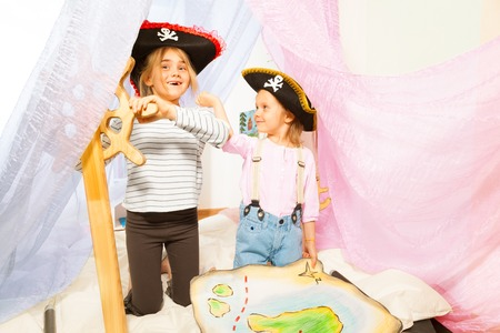 tricorn hat: Two funny girls in pirates three-corned hats, steering the ship with toy wooden helm