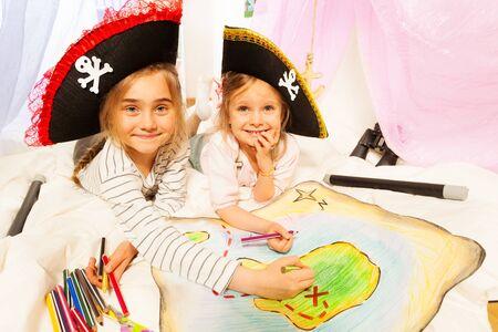 niñas sonriendo: Dos muchachas sonrientes llevando tricornios de piratas, dibujo del mapa de la isla del tesoro con lápices de colores Foto de archivo