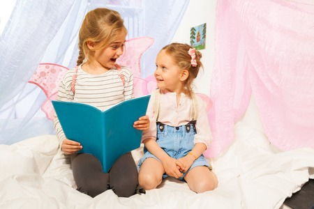 bedtime story: Two happy girls in costumes of little pixies with pink wings, reading bedtime story