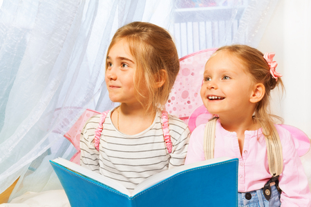 bedtime: Two little girls, beautiful pixies with pink wings, reading fairy-tale before bedtime Stock Photo
