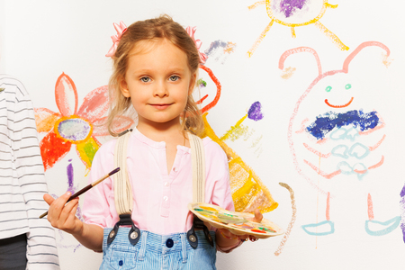 Leuke glimlachende schilder, vijf jaar oud meisje met penseel en palet tekenen kleurrijk beeld