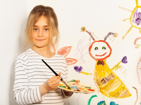 7 year old girl: Young painter, seven years old girl, mixing colors at the pallet for her drawing