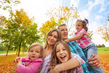 colorful maple trees: Happy family play in the autumn park hugging little kids in sunny weather and colorful maple trees Stock Photo