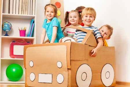 play room: Smiling 5 years old boy drives his friends in toy cardboard car at the kindergarten
