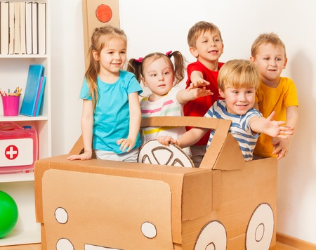 drivers: Five little drivers, boys and girls, playing with handmade cardboard car at the kindergarten Stock Photo