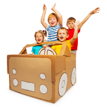 pretend: Four happy kids waving their hands sitting in toy cardboard car, isolated on white