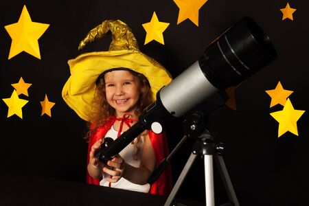 gazer: Happy five years old girl in sky gazer costume with a telescope at a dark starry background