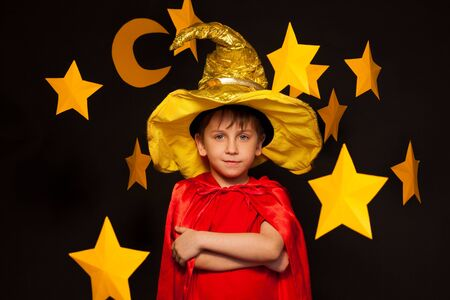 the watcher: Five years old boy in sky watcher costume among big yellow paper stars and moon Stock Photo