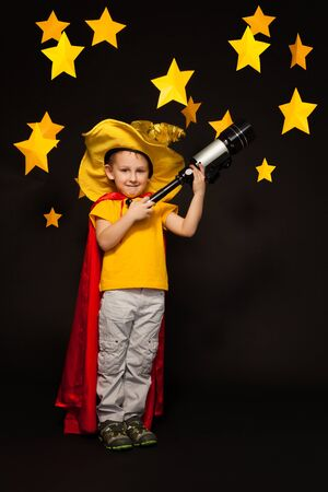 the watcher: Full length photo of boy playing sky watcher with a telescope, standing against black background with paper stars above