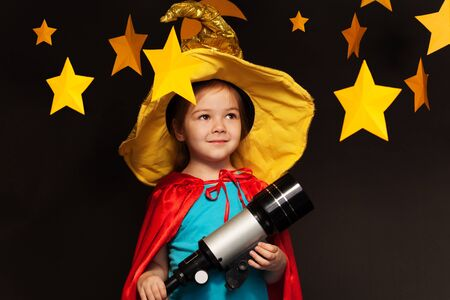 the watcher: Beautiful little girl in sky watcher costume stargazing through a telescope Stock Photo