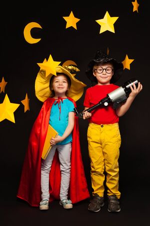 five years old: Full length photo of five years old boy and girl, playing sky watchers with a telescope, standing among handmade stars and moon