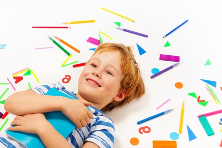 five years old: Close up picture of smiling five years old boy with book, having a rest among heap of stationery