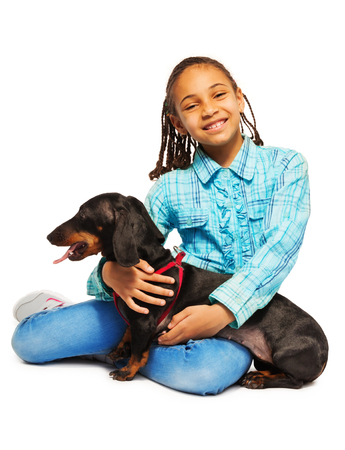 Smiling African girl hugging friendly black dachshund sitting isolated on white
