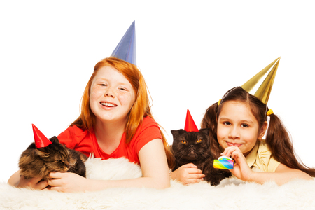 fussy: Two little girls and 2 cats happy lay on the floor wear birthday party caps and blower