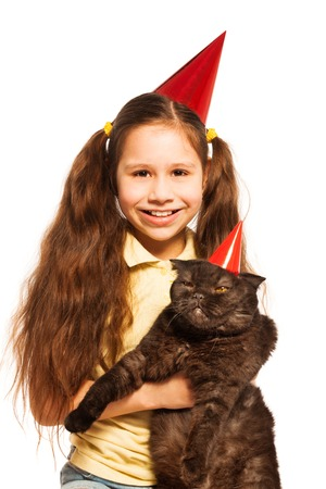 fussy: Happy little girl with black cat and wearing party birthday cap as well as pet isolated on white Stock Photo