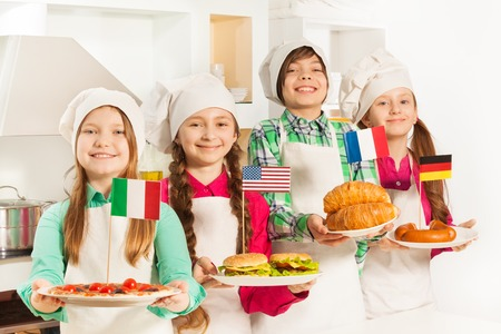 plates of food: Four young cooks holding plates with traditional food of European states and USA in the kitchen Stock Photo