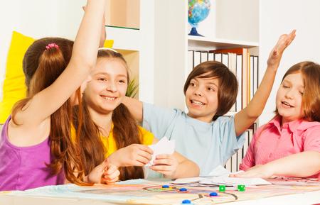 행복 한 아이, 하이브 다섯을주는 게임 테이블에 앉아 방에서 카드 놀이