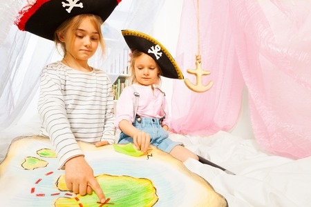roger: Two little pirates, girls in tricorns with jolly Roger, looking for a Treasure Island