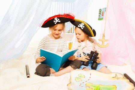 7 year old girl: Two girls in pirates tricorns, reading a fairy-tale, sitting in imagine ship