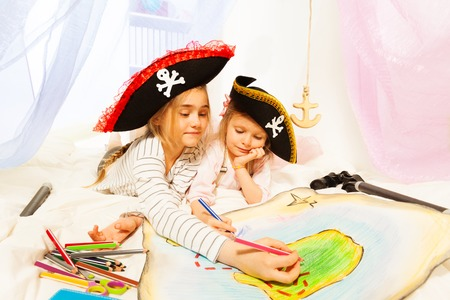 tricorn hat: Two girls in pirates tree-corned hats, drawing the treasure map laying at the imagine ship