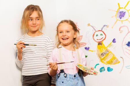 funny picture: Two smiling painters, girls with pallet and brushes drawing funny picture on the wall