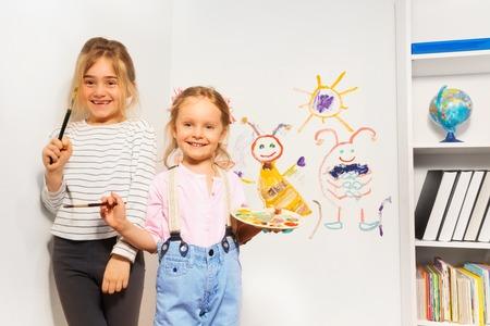 zeichnen: Zwei glückliche Mädchen, junge Maler mit Pinsel und Palette, zeichnen lustiges Bild an der Wand