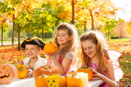 Three kids in costumes crafting Halloween pumpkins in the forest during sunny autumn day