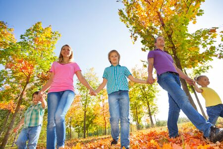 the view from below: View from below of family walking together holding hands in a row in the park during beautiful sunny autumn day