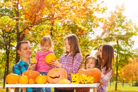 autumn garden: Whole family with three kids and parents prepare for Halloween part sitting in the autumn garden Stock Photo