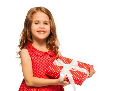 Close portrait of a little girl with curly hair stand with small red present and red dress isolated on white Stock Photo