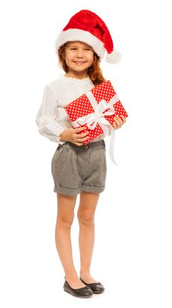full height: Cute smiling little girl with red present with white bow and wearing Christmas Santa hat full height portrait