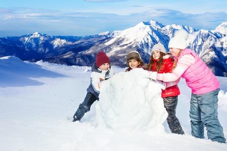 Čtyři kamarádi, jeden chlapec a tři děvčata rolovací velkou sněhovou kouli proti krásné hory krajiny