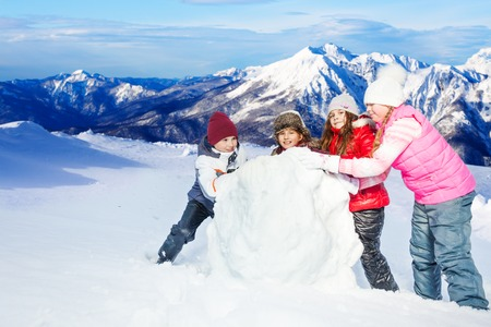 Four friends, one boy and three girls rolling big snowball against beautiful mountains landscape