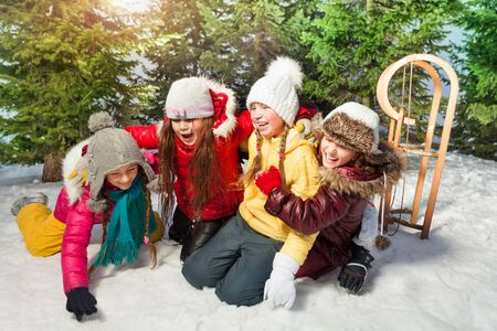 Four girls playing together at winter games standing on their knees on white snow at the forest Stock Photo