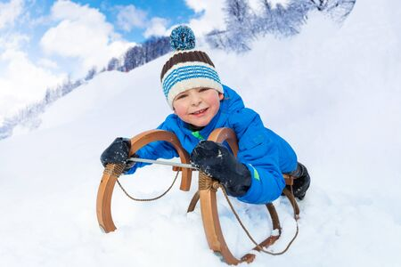 skids: Little boy slide down on sledge smiling and looking at camera Stock Photo