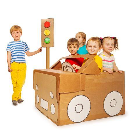 Vijf kleine kinderen studeren verkeersregels spelen met kartonnen auto en verlichting, op wit wordt geïsoleerd Stockfoto