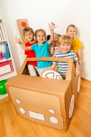 Five happy little friends, boys and girls, playing drivers with handmade cardboard car inside Stock Photo