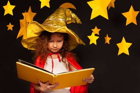 the watcher: Little girl in sky watcher costume reading big book with copy space at the night sky background Stock Photo