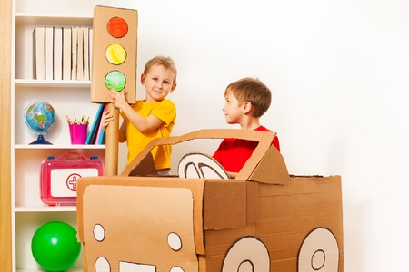 light green: 5 years old boy pointing to the green light of handmade traffic lights while his friend driving toy cardboard car