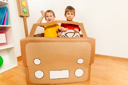 five years old: Two happy friends, five years old boys, driving toy handmade cardboard car at the kindergarten class