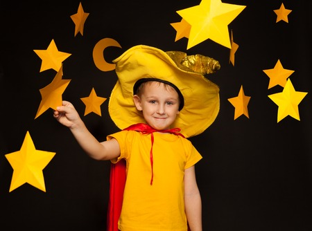 five years': Five years old boy in stargazer costume, standing among paper stars and moon, against black background Stock Photo