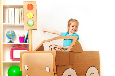 pretend: Smiling four years old girl at the wheel of handmade cardboard car pointing to the toy traffic light by her finger Stock Photo