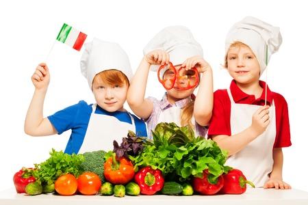 pimenton: Tres cocineros jóvenes, muchacha y muchachos de uniforme, con banderas y anillos de papel italiana, aislados en blanco