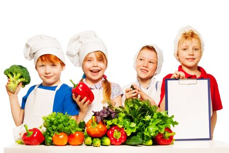 ware: Four smiling cooks, boys and girl with fresh vegetables and blanked clipboard for ingredients list or menu