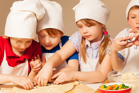 baking: Four young chefs in cooks uniform having fun making homemade cookie with cookie cutters, close-up Stock Photo